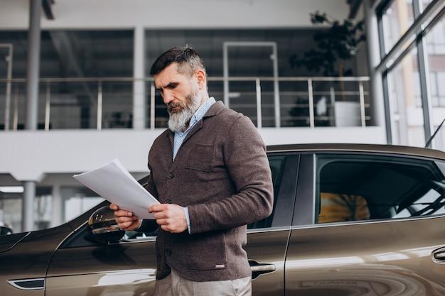 Knappe zakenman die documenten leest over autoverhuur