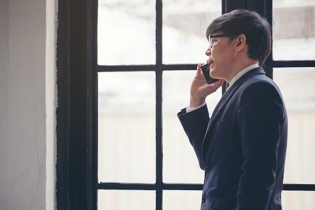 Knappe zakenman die e-mails controleert aan de telefoon in de buurt van het raam