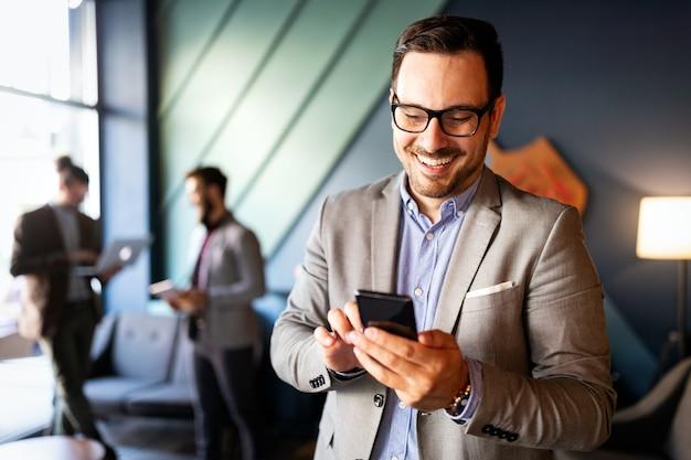 Knappe zakenman die e-mails controleert aan de telefoon in een modern kantoor