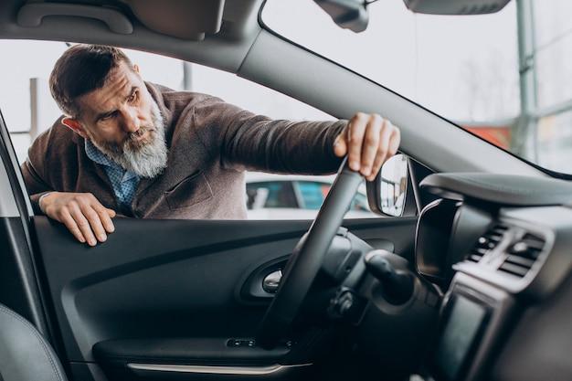 Knappe zakenman die een auto kiest in de autoshowroom