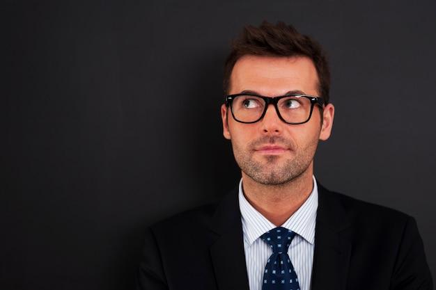 Knappe zakenman die een bril draagt die omhoog kijkt