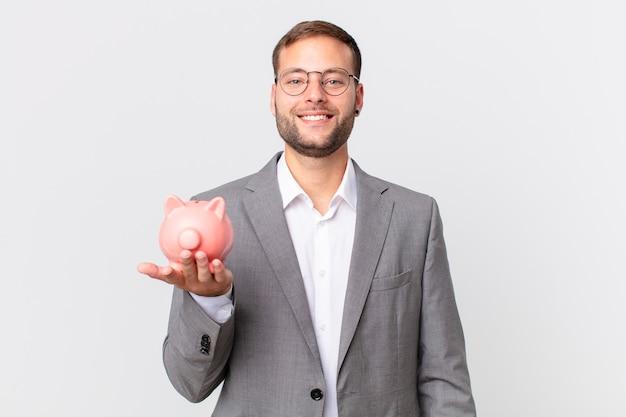 Knappe zakenman die een spaarvarken houdt. spaarconcept