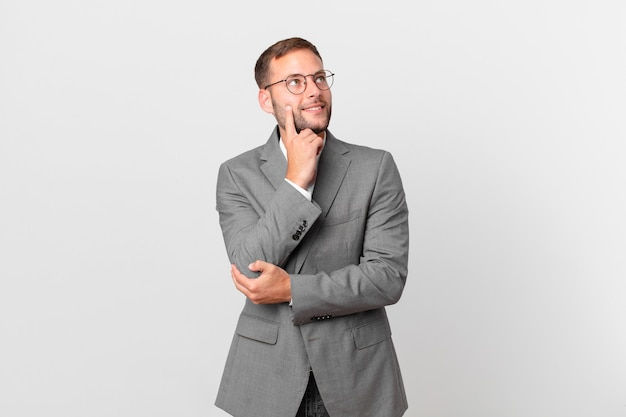 Knappe zakenman die gelukkig glimlacht en dagdroomt of twijfelt