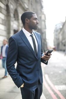 Knappe zakenman die in de straat loopt, die zijn telefoon controleert