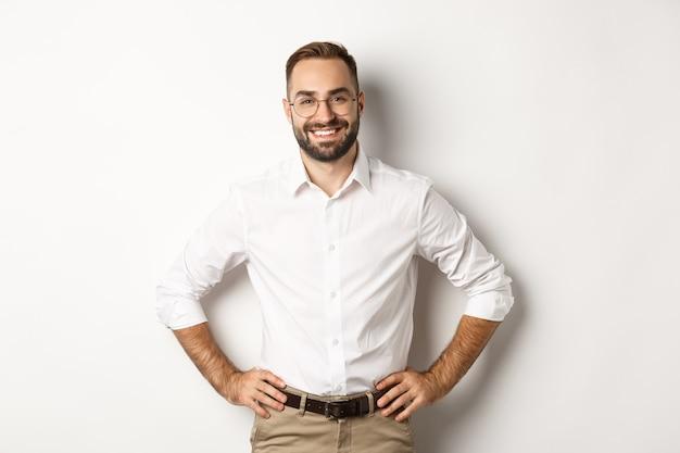 Knappe zakenman die in glazen tevreden kijkt, glimlachend en hand in hand op taille kijkt, die zich over witte achtergrond bevindt.