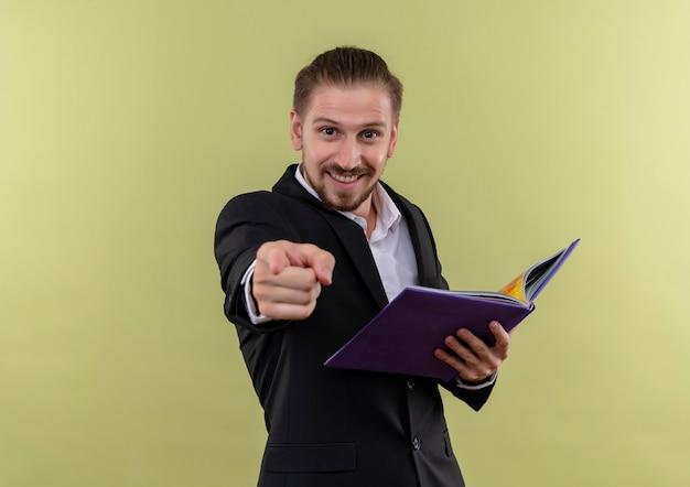 Knappe zakenman die in het notitieboekje van de zwart kostuumholding camera bekijkt die met vinger glimlachen die status over olijfachtergrond richt