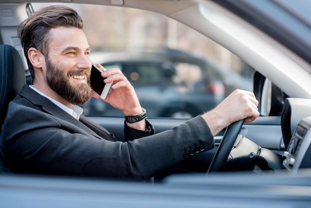Knappe zakenman die met de telefoon praat tijdens het autorijden in de stad