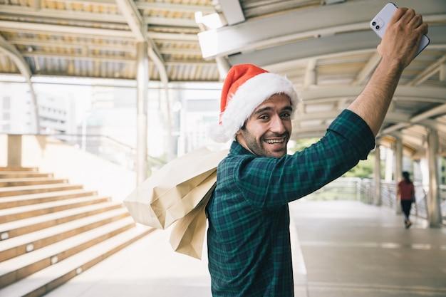 Knappe zakenman die met een papieren zak winkelt en smartphone gebruikt voor betaalproducten in een winkelcentrum in het hart van het stadsbeeld