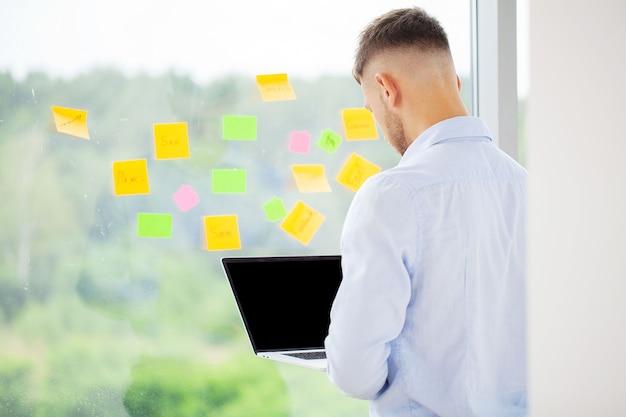 Knappe zakenman die met laptop in bureau werkt.