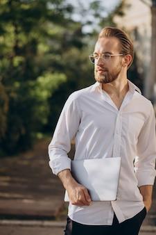 Knappe zakenman die met laptop loopt