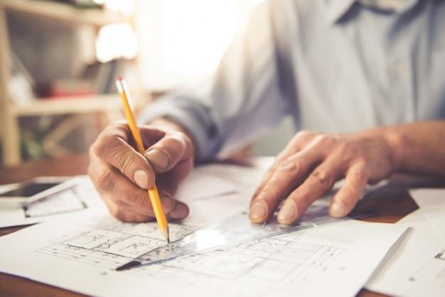 Knappe zakenman die met ontwerpen in bureau werkt.
