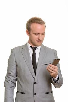 Knappe zakenman die mobiele telefoon houdt die tegen witte muur wordt geïsoleerd