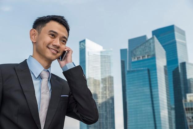 Knappe zakenman die mobiele telefoon spreekt in het kantoorgebouw van zijn bedrijf, model is een aziatisch mannetje