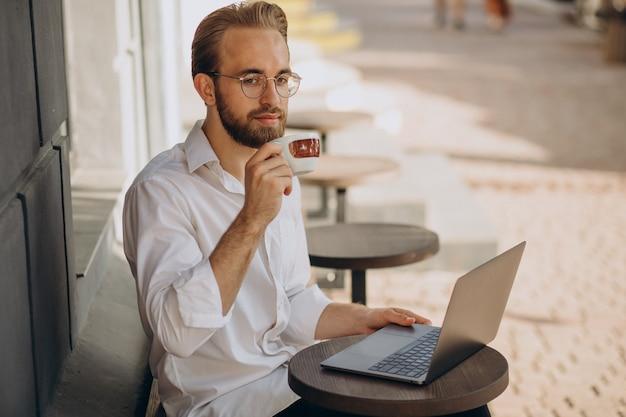 Knappe zakenman die online op de computer werkt vanuit de coffeeshop