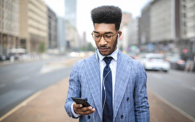 Knappe zakenman die oortelefoons met zijn telefoon met behulp van te roepen
