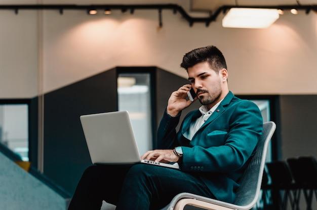Knappe zakenman die op de telefoon spreekt en met laptop in bureau werkt.
