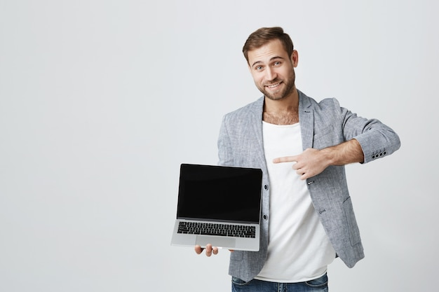 Knappe zakenman die op laptop het scherm richt