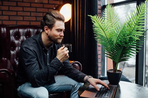 Knappe zakenman die op laptop werkt, kopje koffie of latte vasthoudt in modern café.