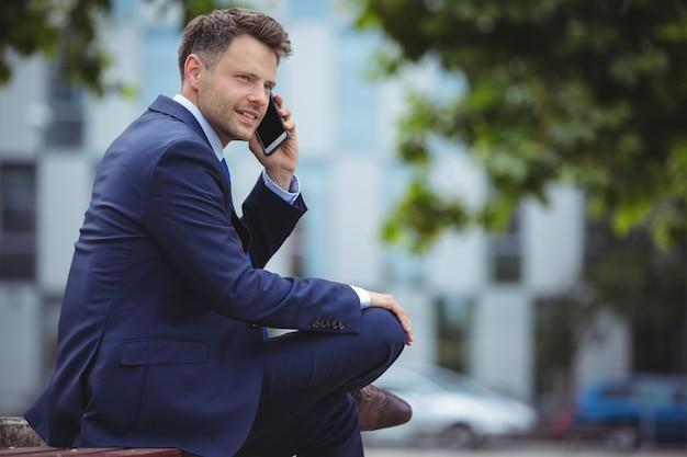 Knappe zakenman die op mobiele telefoon spreekt