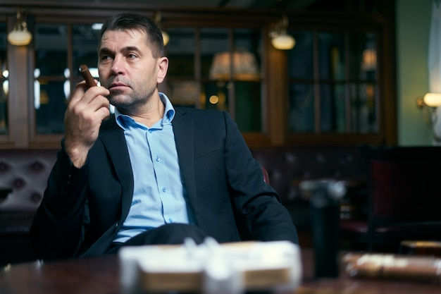 Knappe zakenman die rokende sigaar in een bar begint