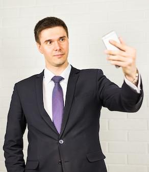 Knappe zakenman die selfie foto op smartphone maken