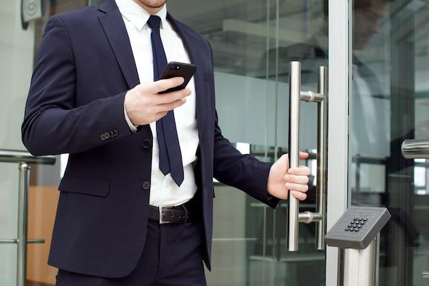Knappe zakenman die smartphone in het bureau gebruiken.