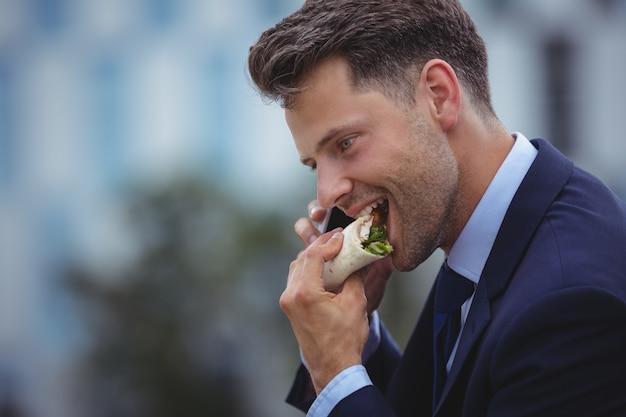 Knappe zakenman die snacks eet