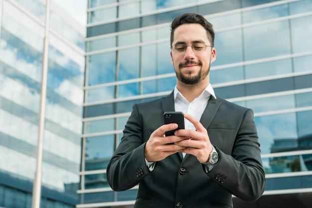 Knappe zakenman die van tekstoverseinen op mobiele telefoon geniet