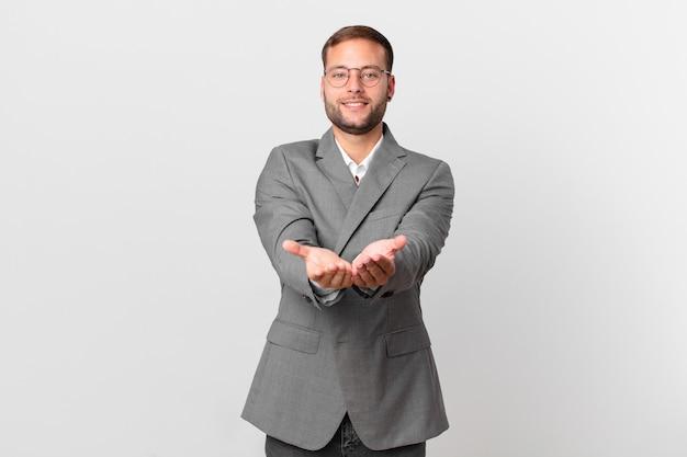 Knappe zakenman die vrolijk glimlacht met vriendelijk en een concept aanbiedt en toont