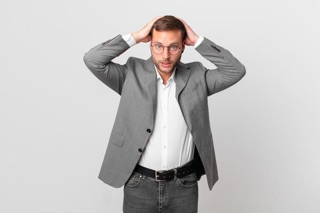 Knappe zakenman die zich gestrest, angstig of bang voelt, met de handen op het hoofd