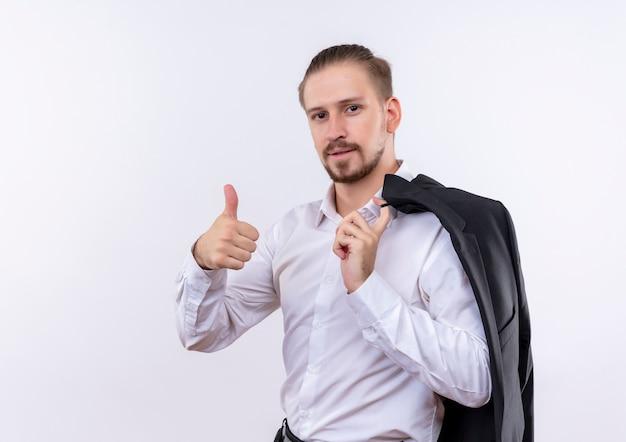 Knappe zakenman die zijn jasje op schouder draagt die camera met zekere glimlach bekijkt die duimen toont die zich over witte achtergrond bevinden