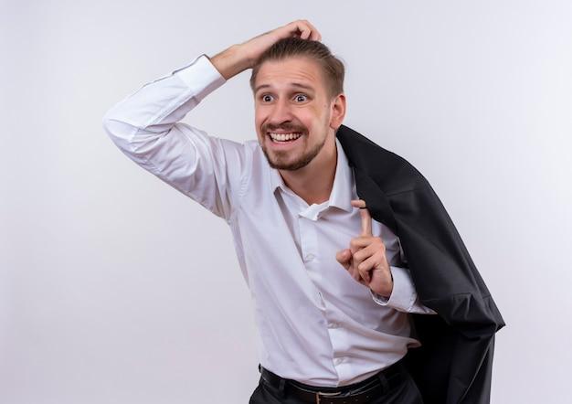 Knappe zakenman die zijn jasje op schouder draagt die opzij verward en zeer angstig status over witte achtergrond kijkt