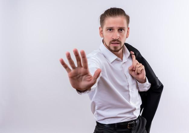 Knappe zakenman die zijn jasje op schouder draagt die stopbord met hand maakt die met ernstig gezicht over witte achtergrond kijkt