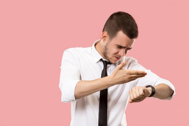 Knappe zakenman die zijn polshorloge controleert die op roze achtergrond wordt geïsoleerd.