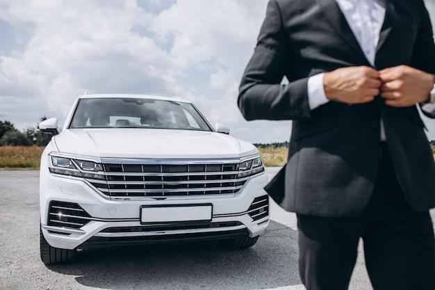 Knappe zakenman door de witte auto