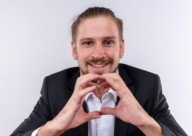 Knappe zakenman dragen pak aking hart gebaar met vingers kijken cmera met glimlach op gezicht staande op witte achtergrond