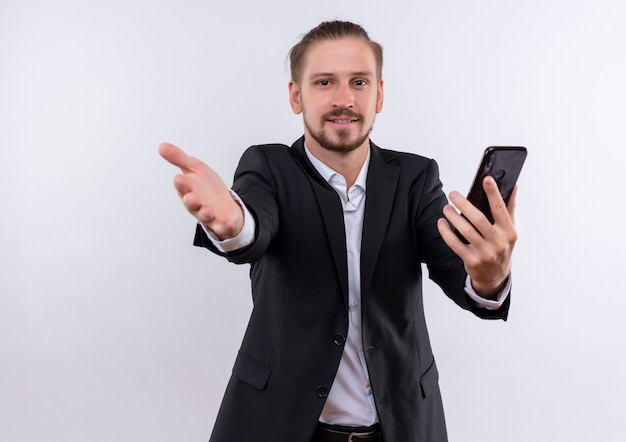 Knappe zakenman dragen pak bedrijf smartphone verwelkomen gebaar met hand glimlachend vriendelijk kijken camera staande op witte achtergrond