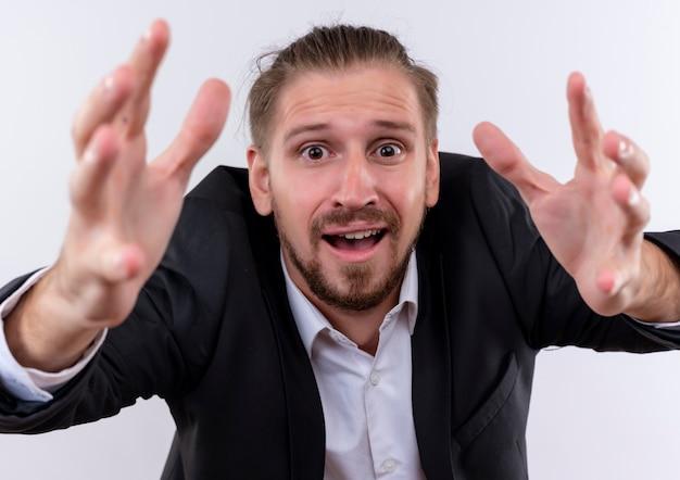 Knappe zakenman dragen pak camera kijken met armen uit met hoop expressie staande op witte achtergrond