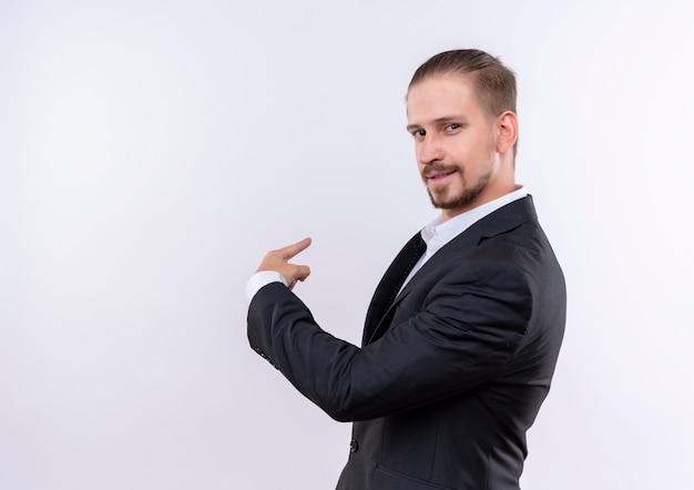 Knappe zakenman dragen pak camera kijken met zelfverzekerde glimlach wijzend terug staande op witte achtergrond