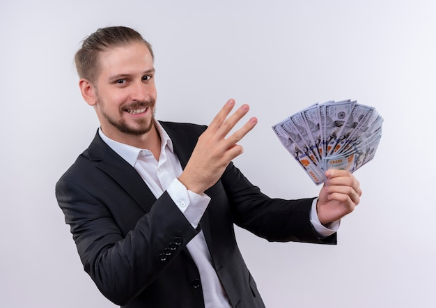 Knappe zakenman dragen pak contant geld tonen en piinting met vingers nummer drie op zoek verrast staande op witte achtergrond