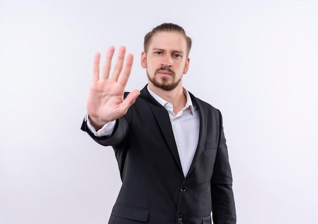 Knappe zakenman dragen pak stopbord met open hand kijken camera met ernstig gezicht staande op witte achtergrond