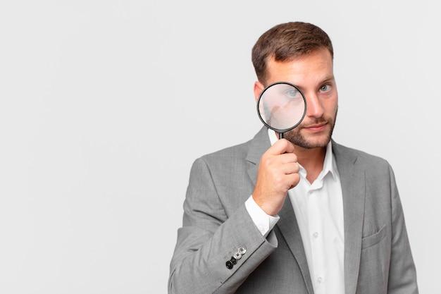 Knappe zakenman finfing met een vergrootglas