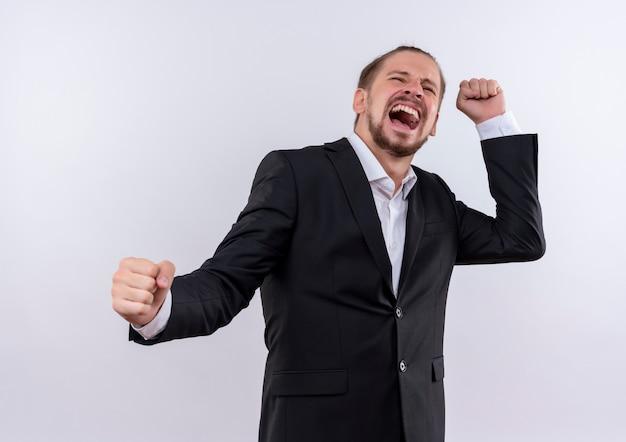 Knappe zakenman gekleed pak gebalde vuisten gek gelukkig staande op witte achtergrond