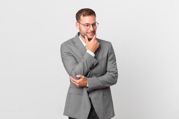 Knappe zakenman glimlachend met een gelukkige, zelfverzekerde uitdrukking met de hand op de kin