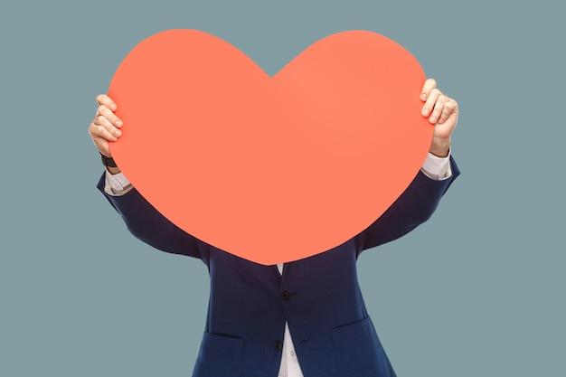 Knappe zakenman in blauwe jas die staat en vasthoudt en de rode grote hartvorm voor het gezicht bedekt voor kopieerruimte. binnen, studio-opname geïsoleerd op lichtblauwe achtergrond.