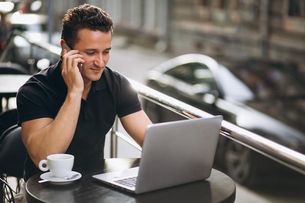 Knappe zakenman in een café met laptop