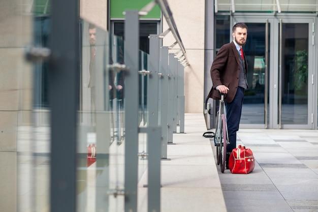 Knappe zakenman in een jas en een rode stropdas en zijn fiets op stadsstraten. rode zak ligt naast. het concept van de moderne levensstijl van jonge mannen