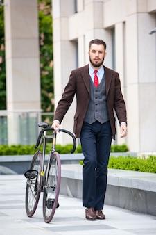 Knappe zakenman in een jas en een rode stropdas en zijn fiets op stadsstraten.