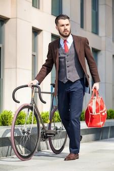 Knappe zakenman in een jas en een rode tas en zijn fiets op stadsstraten. het concept van de moderne levensstijl van jonge mannen