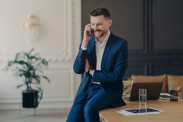 Knappe zakenman in formele kleding die telefonisch op kantoor praat en blij is om goed nieuws over het project te horen terwijl hij op het bureau zit met een laptop in een luxe appartement of kantoor. bedrijfsconcept